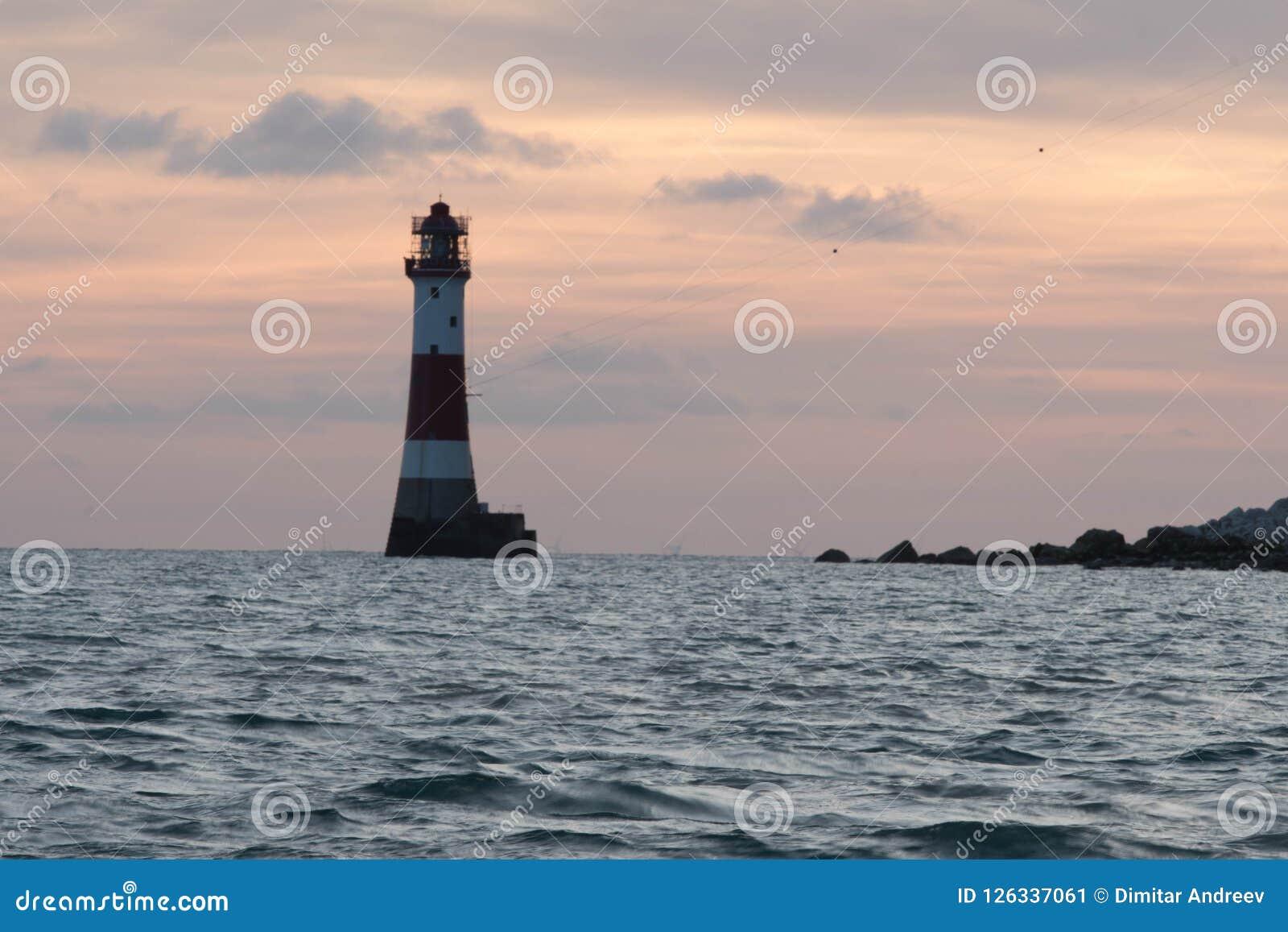 19/09/2018 Eastbourne, het Verenigd Koninkrijk Kiezelachtige Hoofdvuurtoren in het overzees en de zonsondergang op de achtergrond