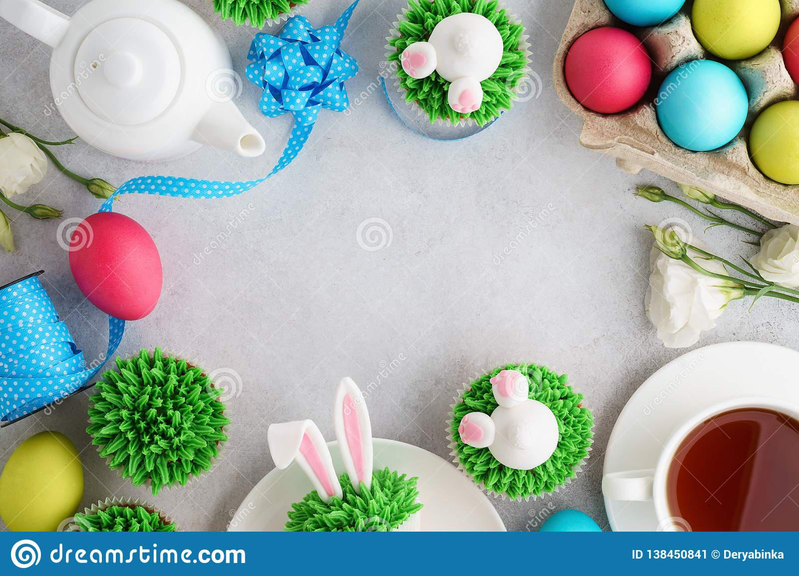 Easter background with bunny cupcakes, tea and painted eggs