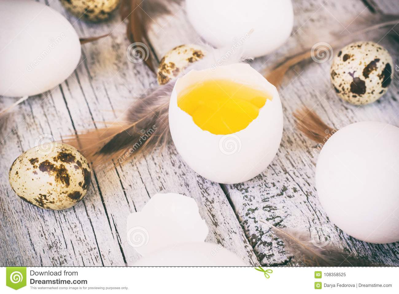 easter background with chicken quail one broken eggs and feathers on white wooden table, food top view