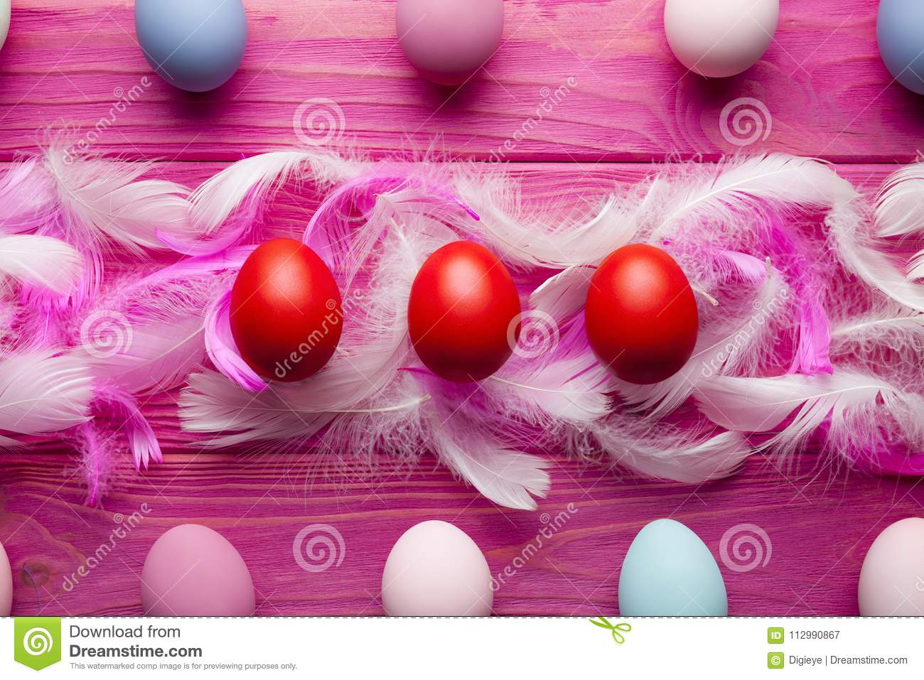 Easter background - colored eggs and feathers on pink background