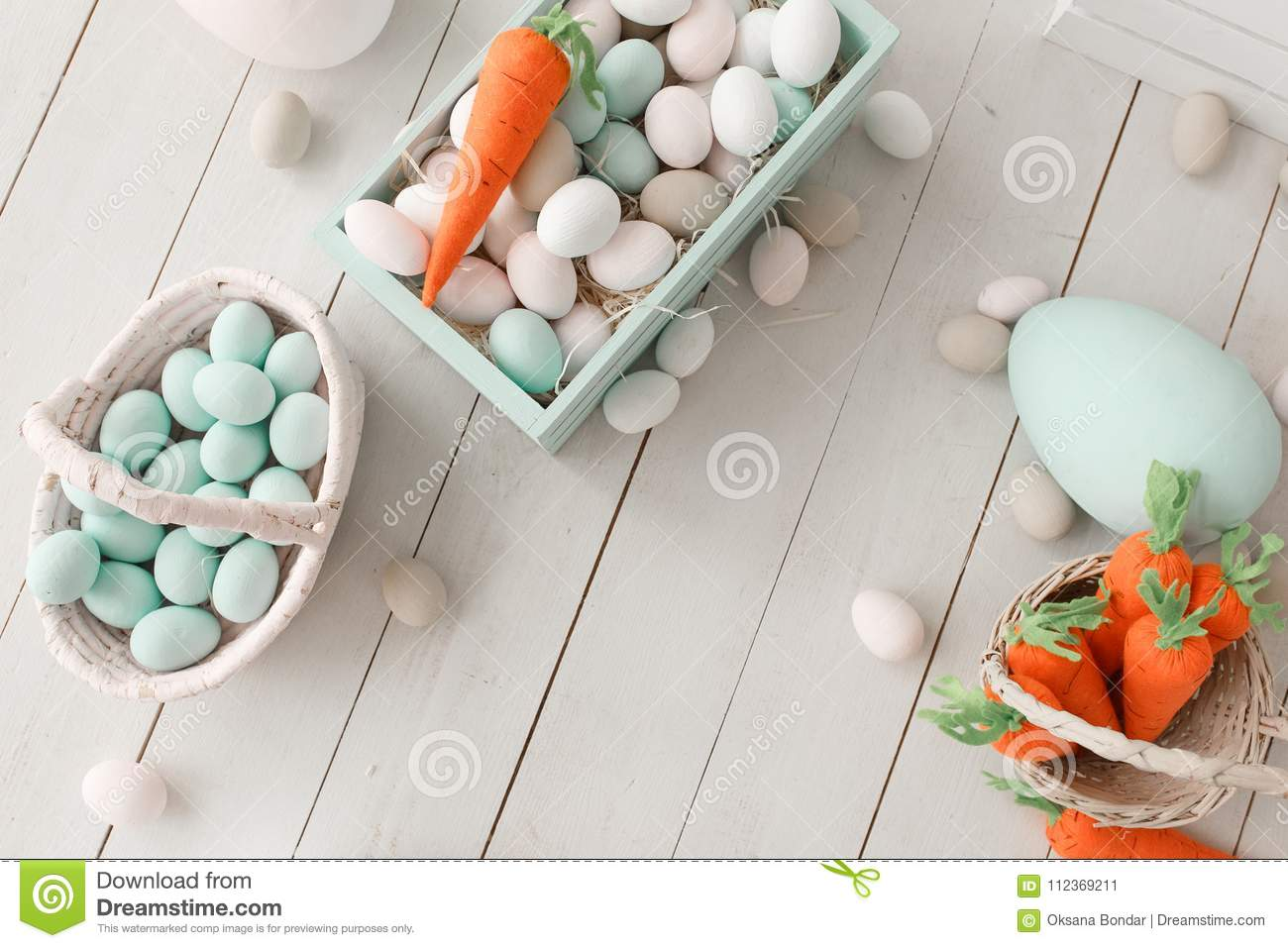 Easter background with colorful eggs and yellow orange carrots over white wood. Top view with copy space