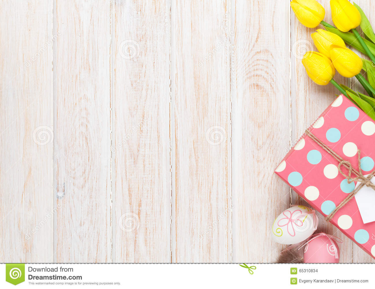 Easter background with colorful eggs and yellow tulips