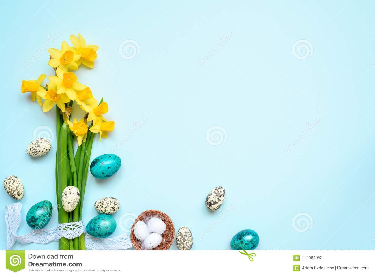 Easter Background with easter eggs and spring flowers on blue background. top view