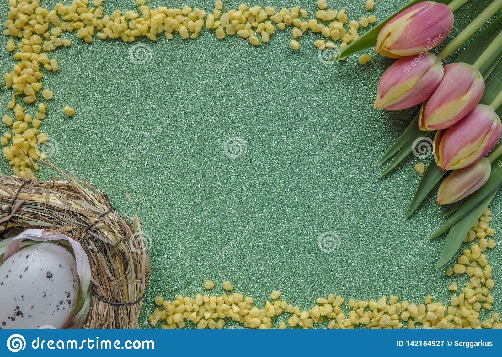 Easter background with red-yellowk tulips and egg on green glitter background with copy space