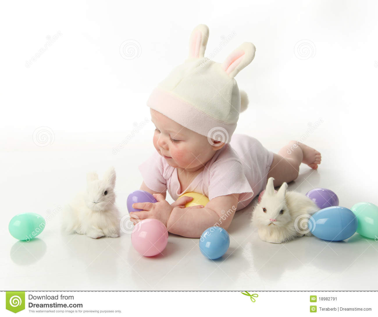 Portrait of a cute baby dressed in Easter bunny ears with eggs.