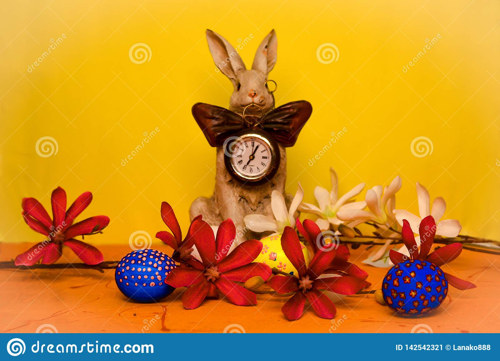 Easter bunny with a clock on his chest surrounded by spring flowers with blue, yellow and white eggs