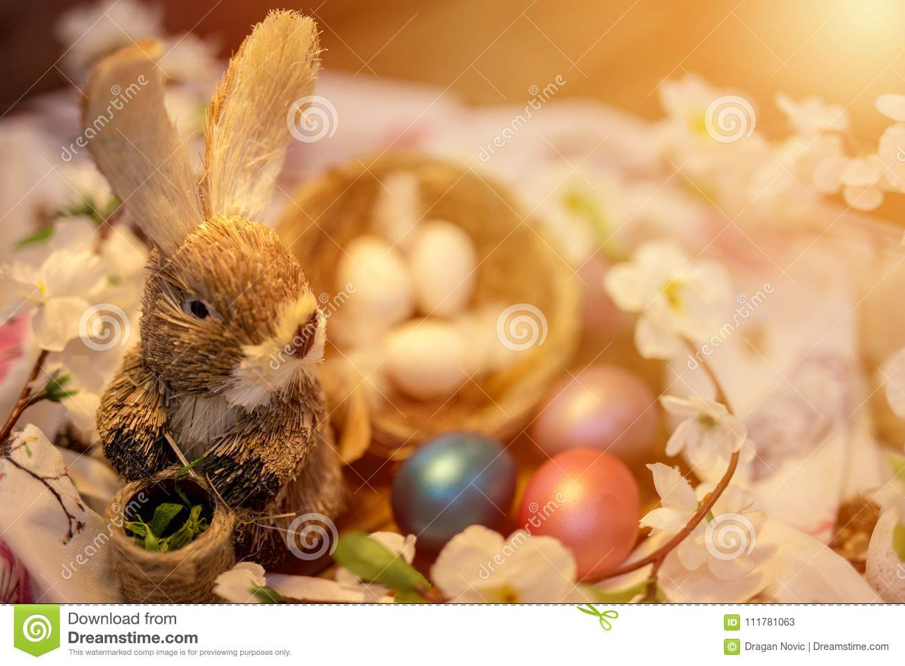 Easter bunny sitting next to a nest filled with colorful easter