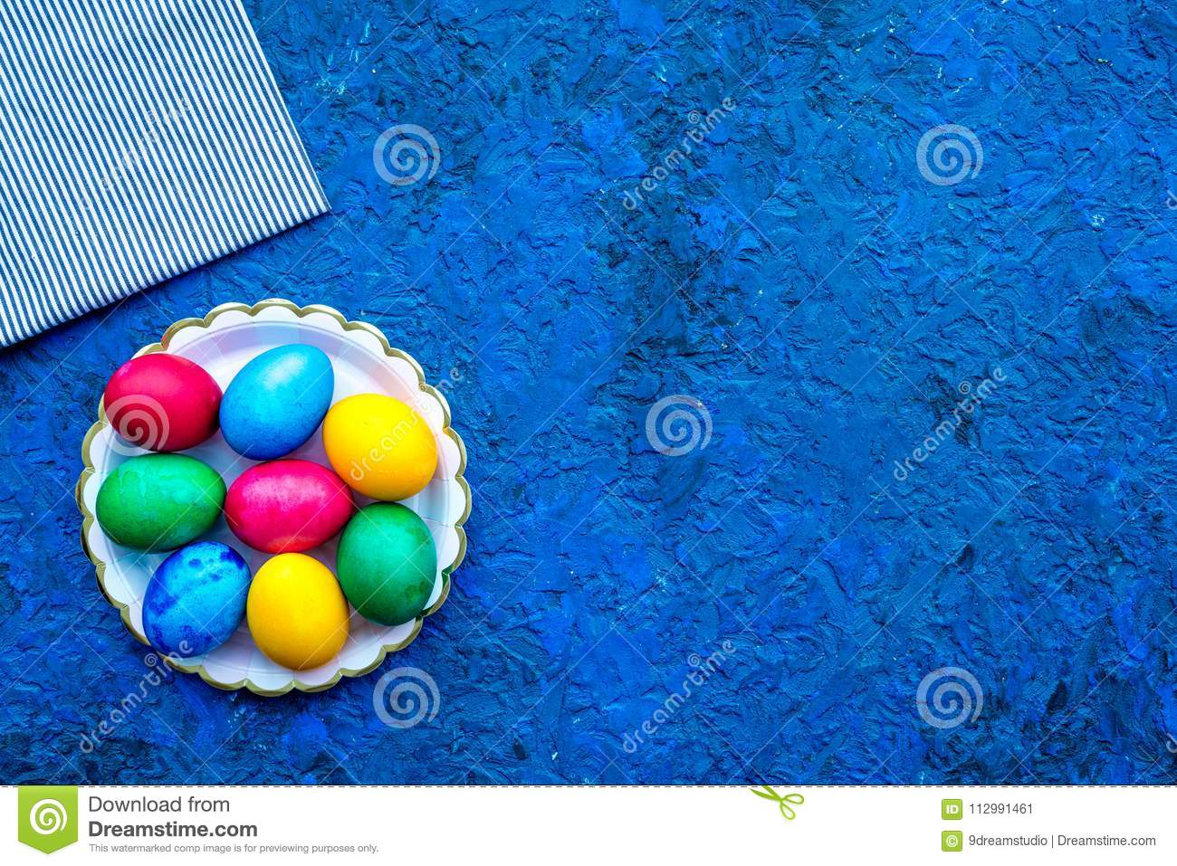 Easter celebration with colorful eggs. Blue background top view mock up