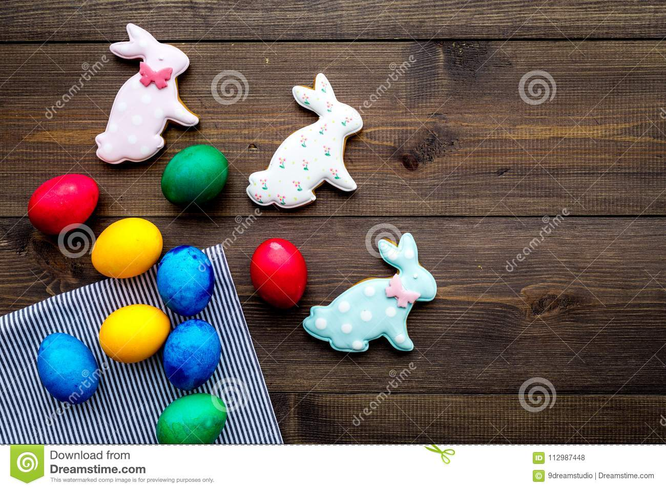 Easter celebration with colorful eggs and gingerbread in shape of easter bunny and carrot. Wooden background top view