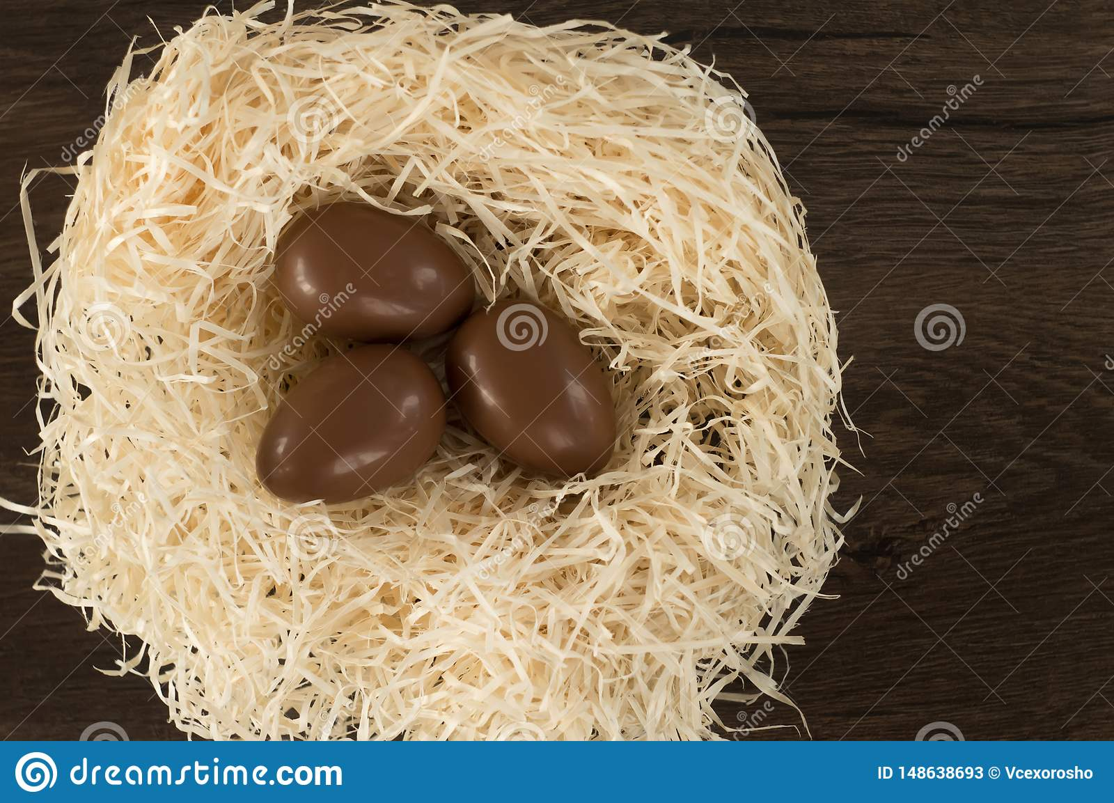 Easter. Chocolate eggs lie in a nest on a wooden brown table