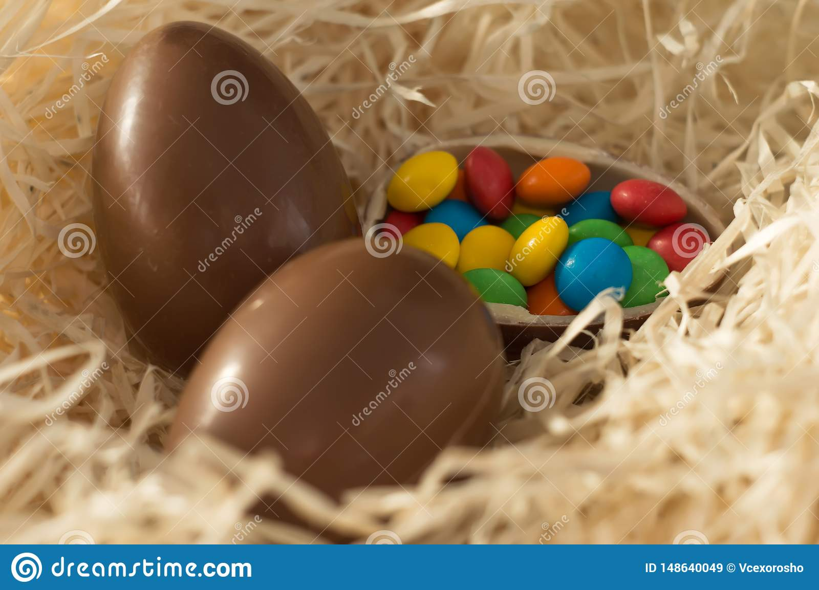 Easter. Chocolate eggs with multicolored candies lie in a nest on a wooden white table