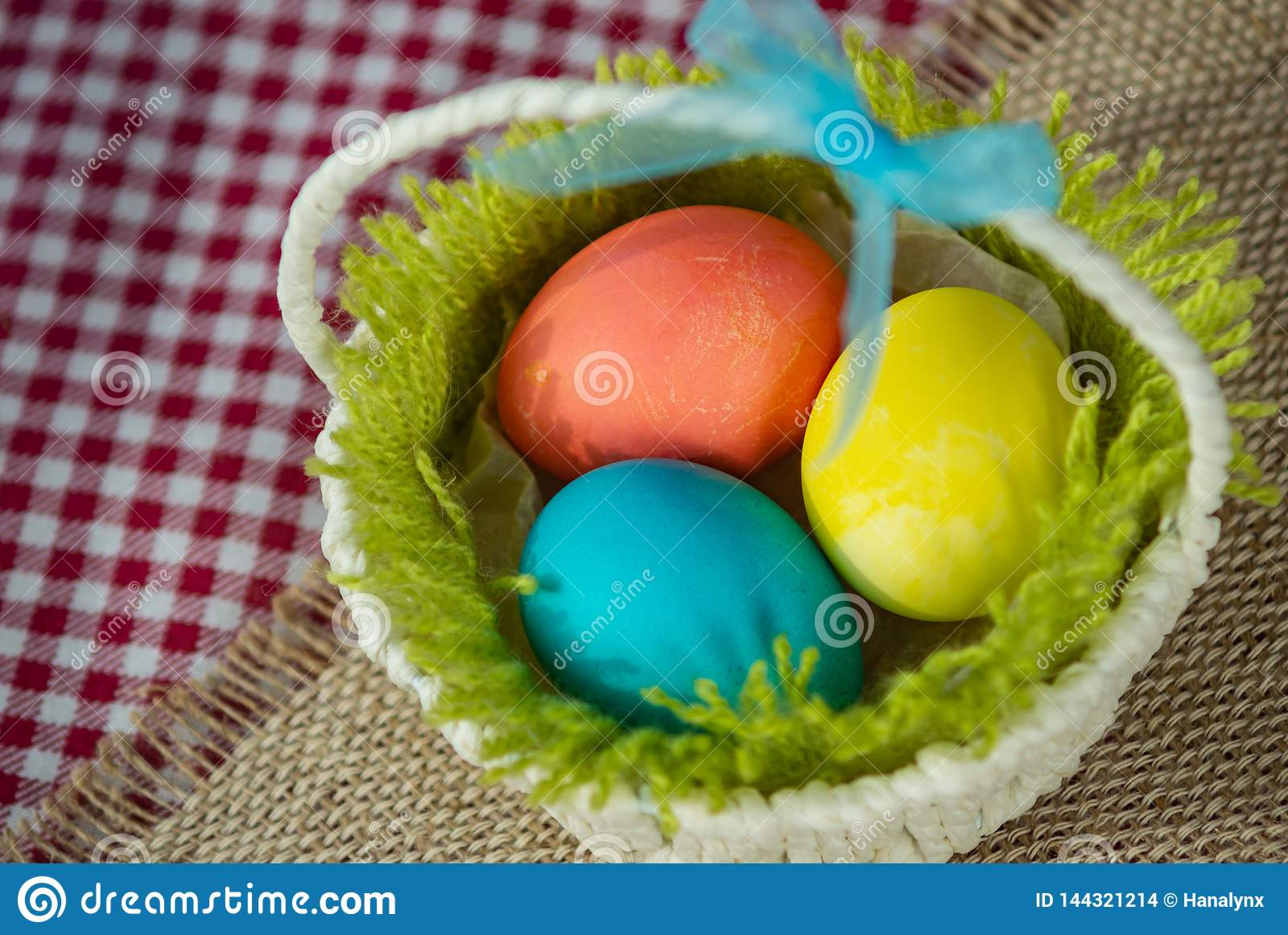 Easter colored eggs in a basket on a canvas napkin and checkered tablecloth