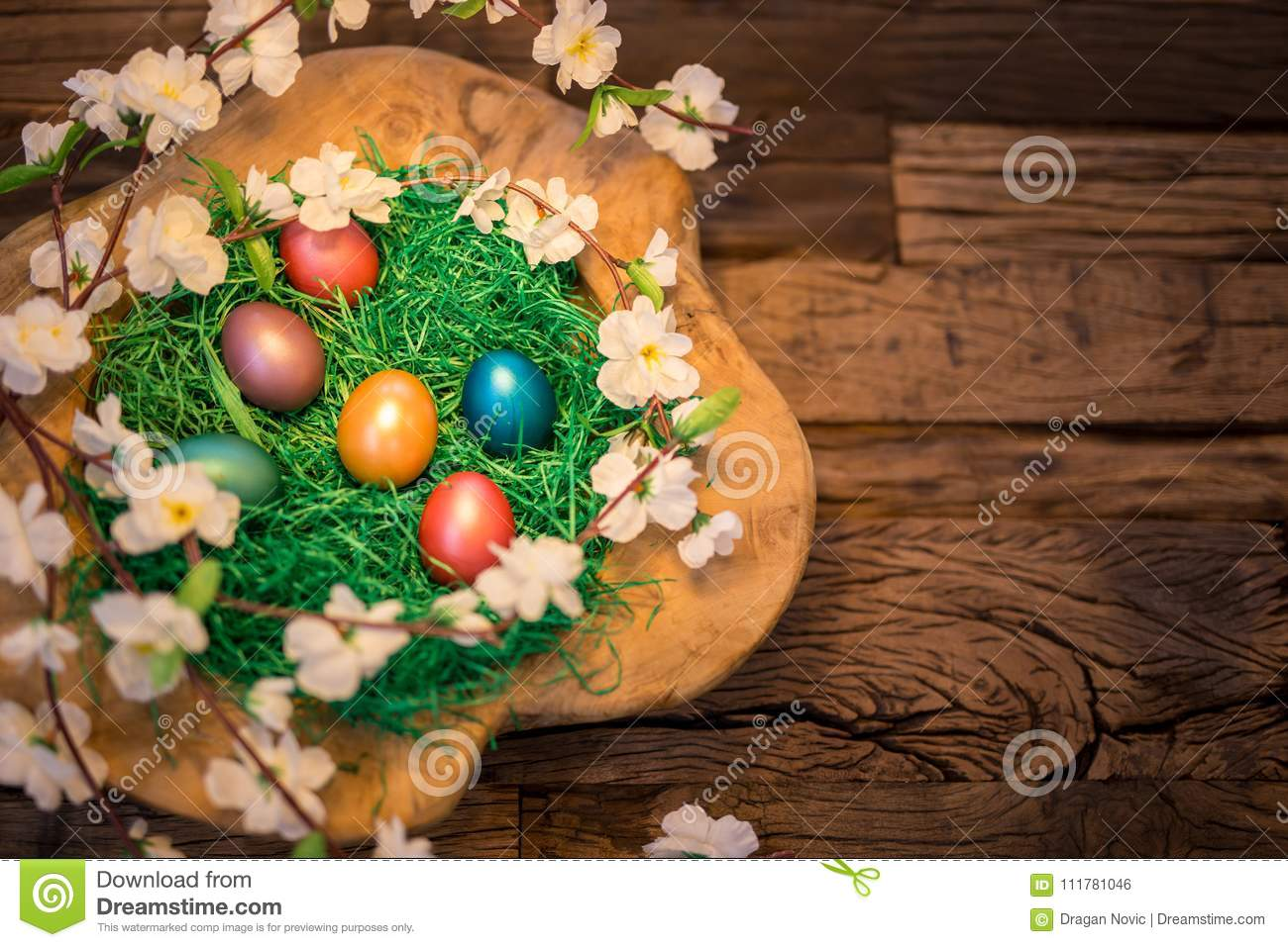 Easter colorful eggs in a nest on a wooden background