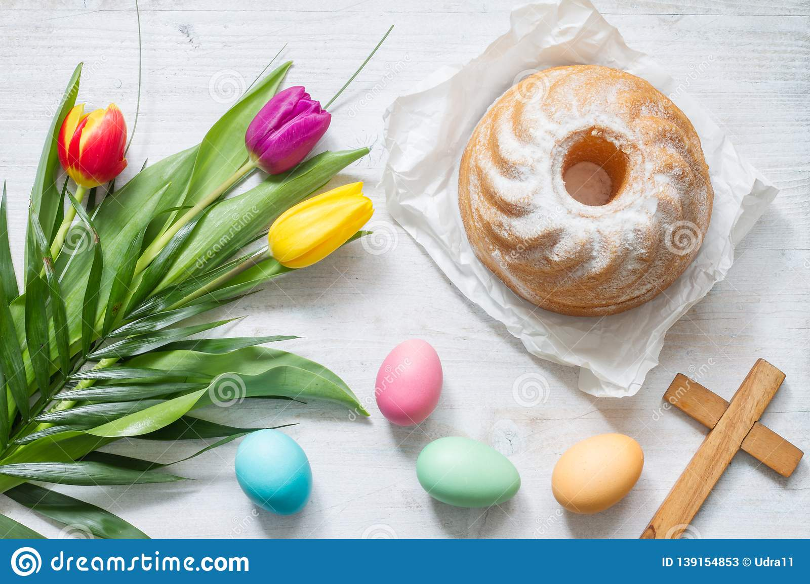 Easter colorful spring tulips with palm cross cake and eggs decoration on white wooden natural background