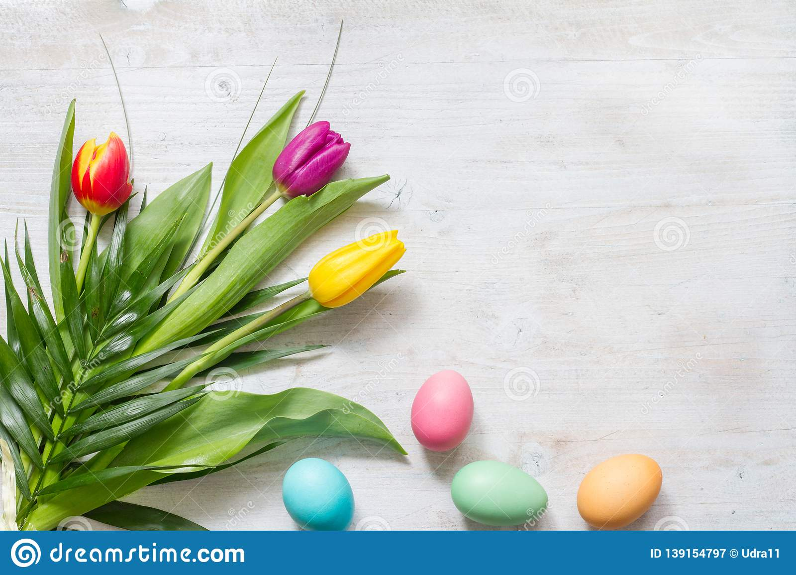 Easter colorful spring tulips with palm and eggs decoration on white wooden natural background