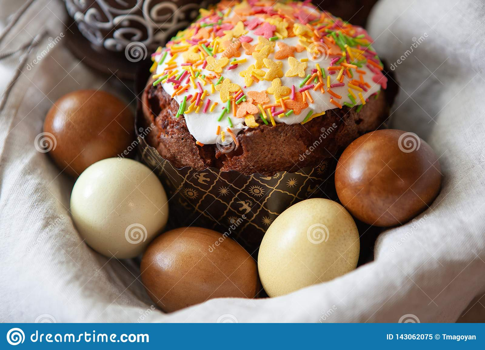 Easter composition with appetizing, beautifully decorated Easter cake, dyed eggs in a basket on linen fabric, close-up, side view