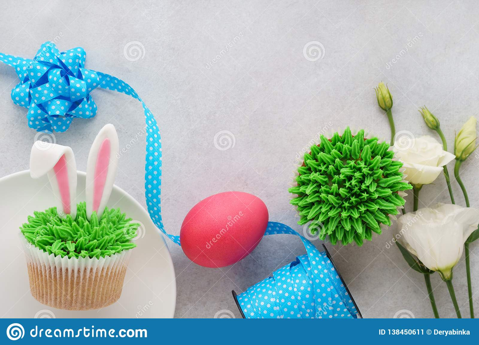 Easter concept with bunny ears cupcakes, blue ribbon, pink egg