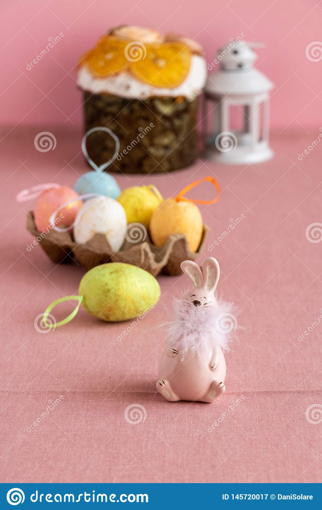 Easter decor with colorful eggs, Easter cake and a pink bunny.