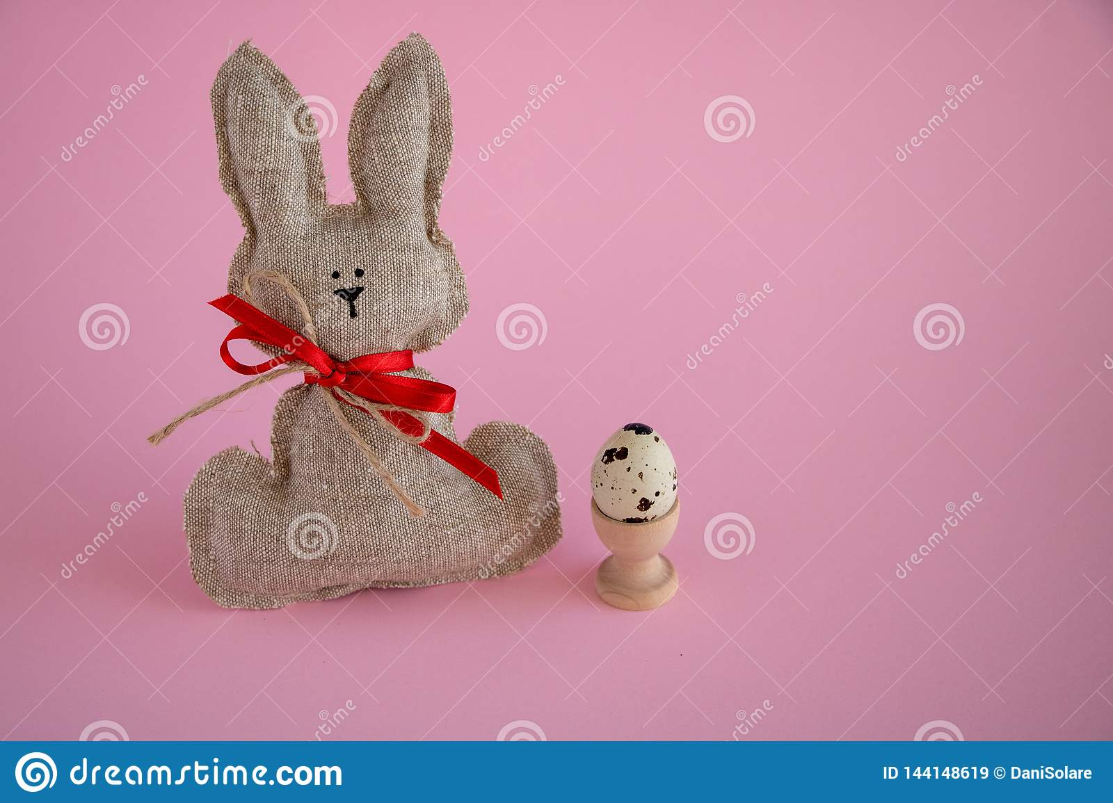 Easter decorations on a pink background with a hand made Easter bunny