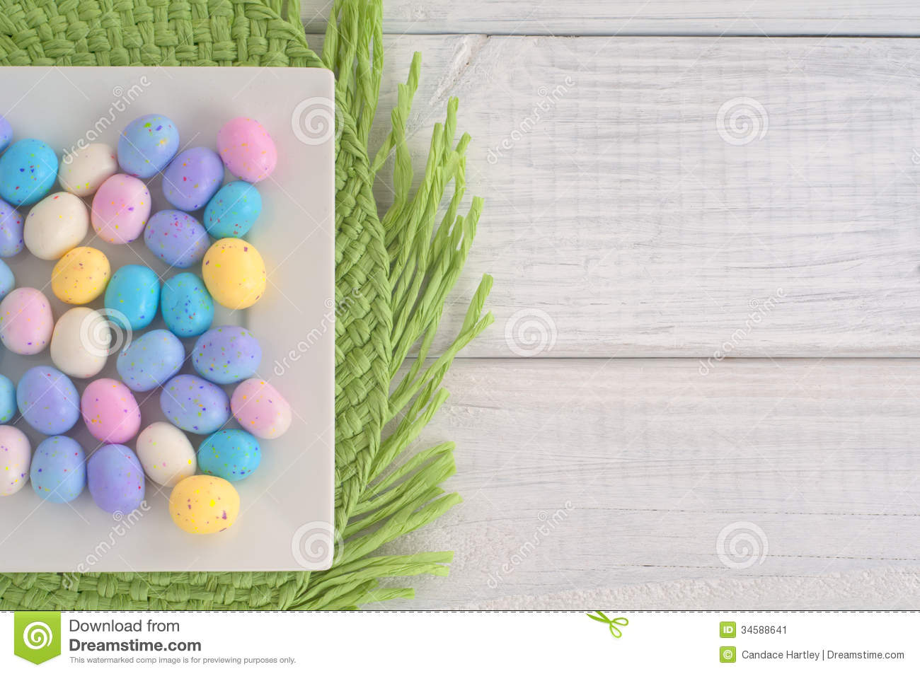 Easter egg candy on Square Dish on Green Placemat on White Wood Boards as Background