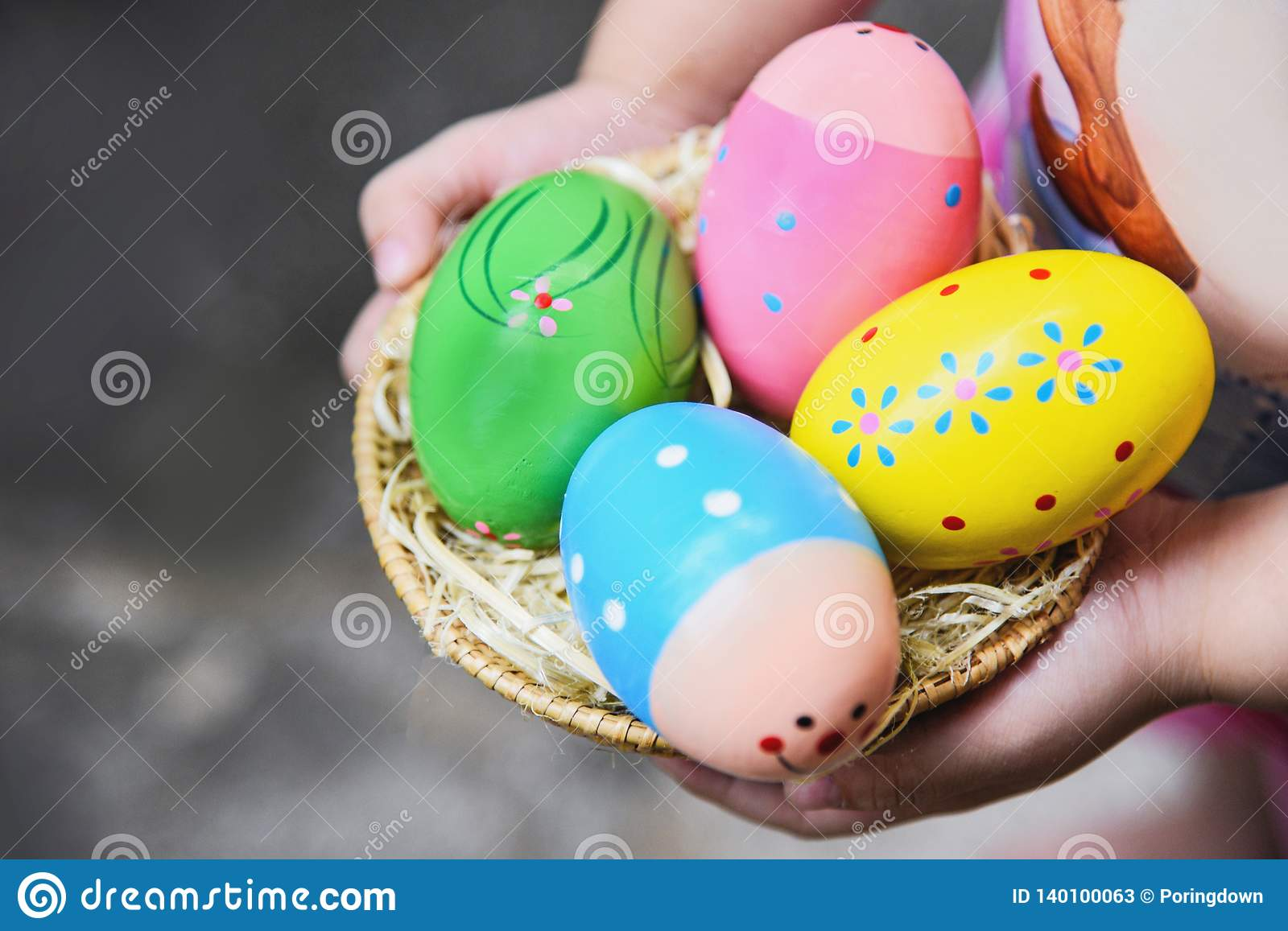 Easter egg hunt colorful in basket on hand little girl Egg painted in the nest