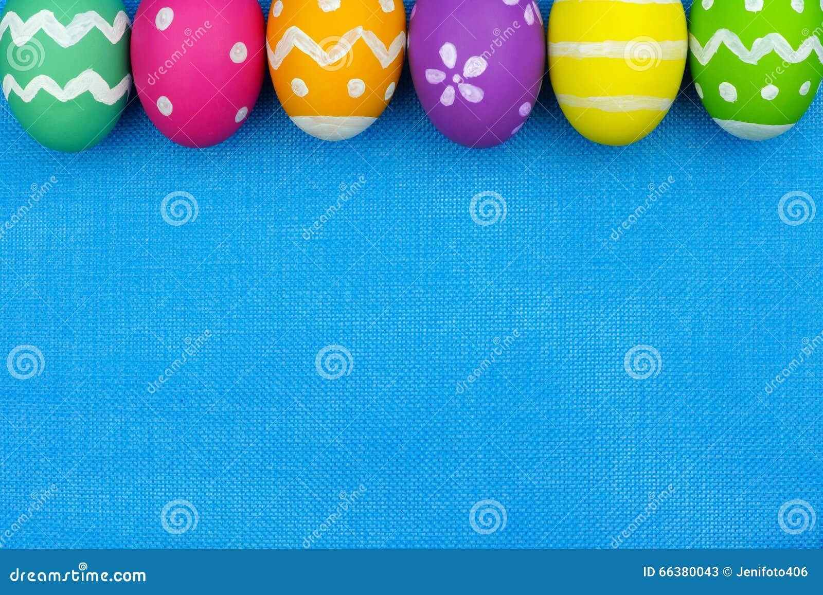 Easter egg top border over blue burlap background