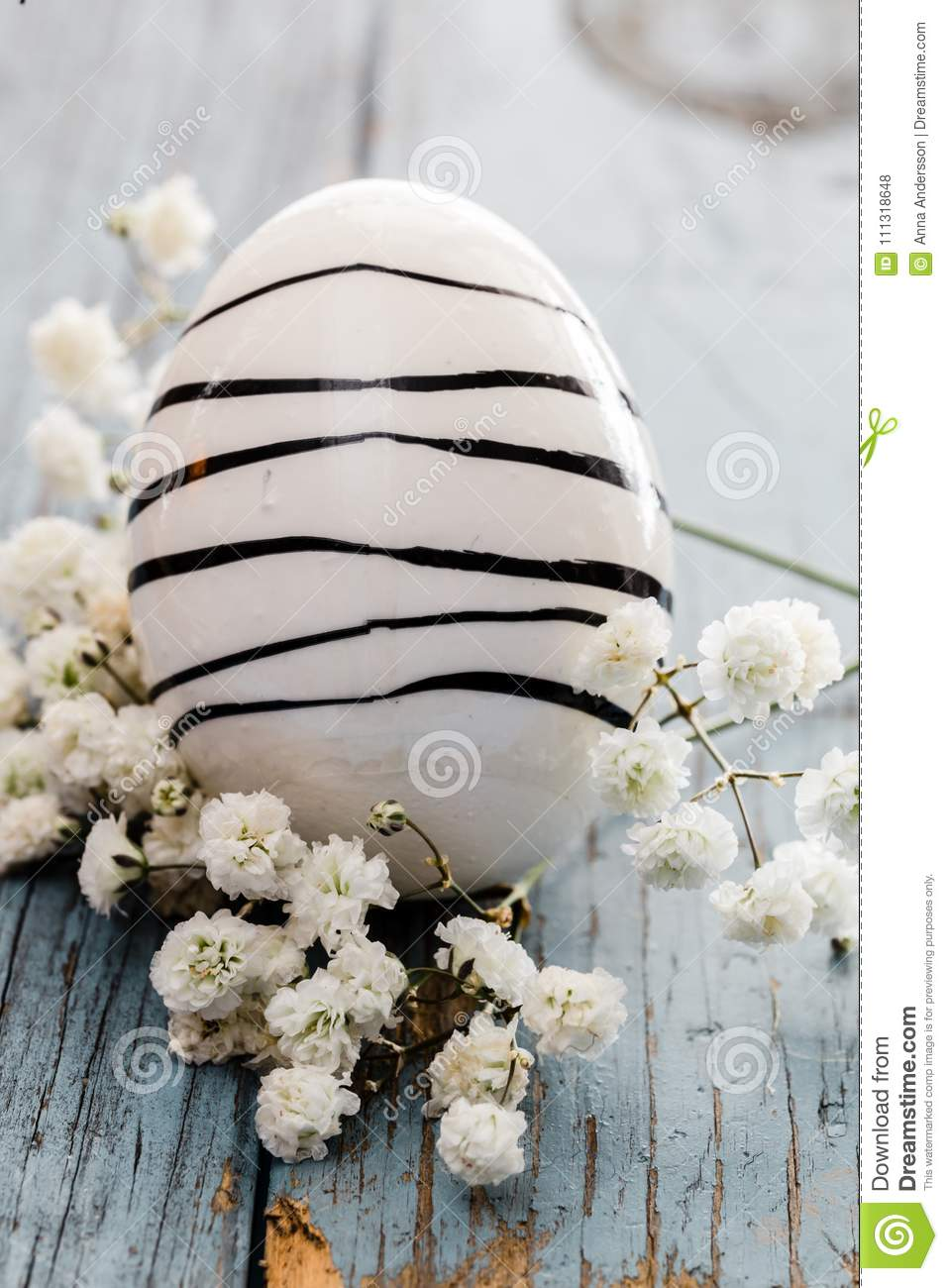 Painted easter egg with black stripes on blue wooden table and with white flowers