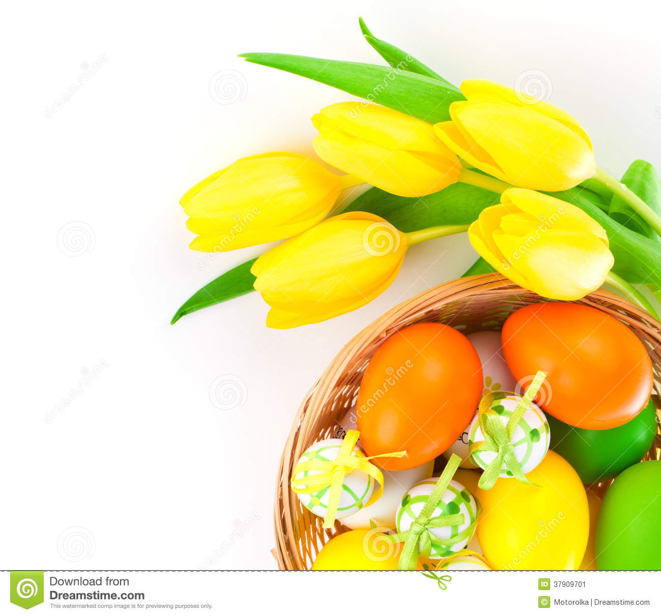 Easter eggs in a basket with yellow tulips flowers
