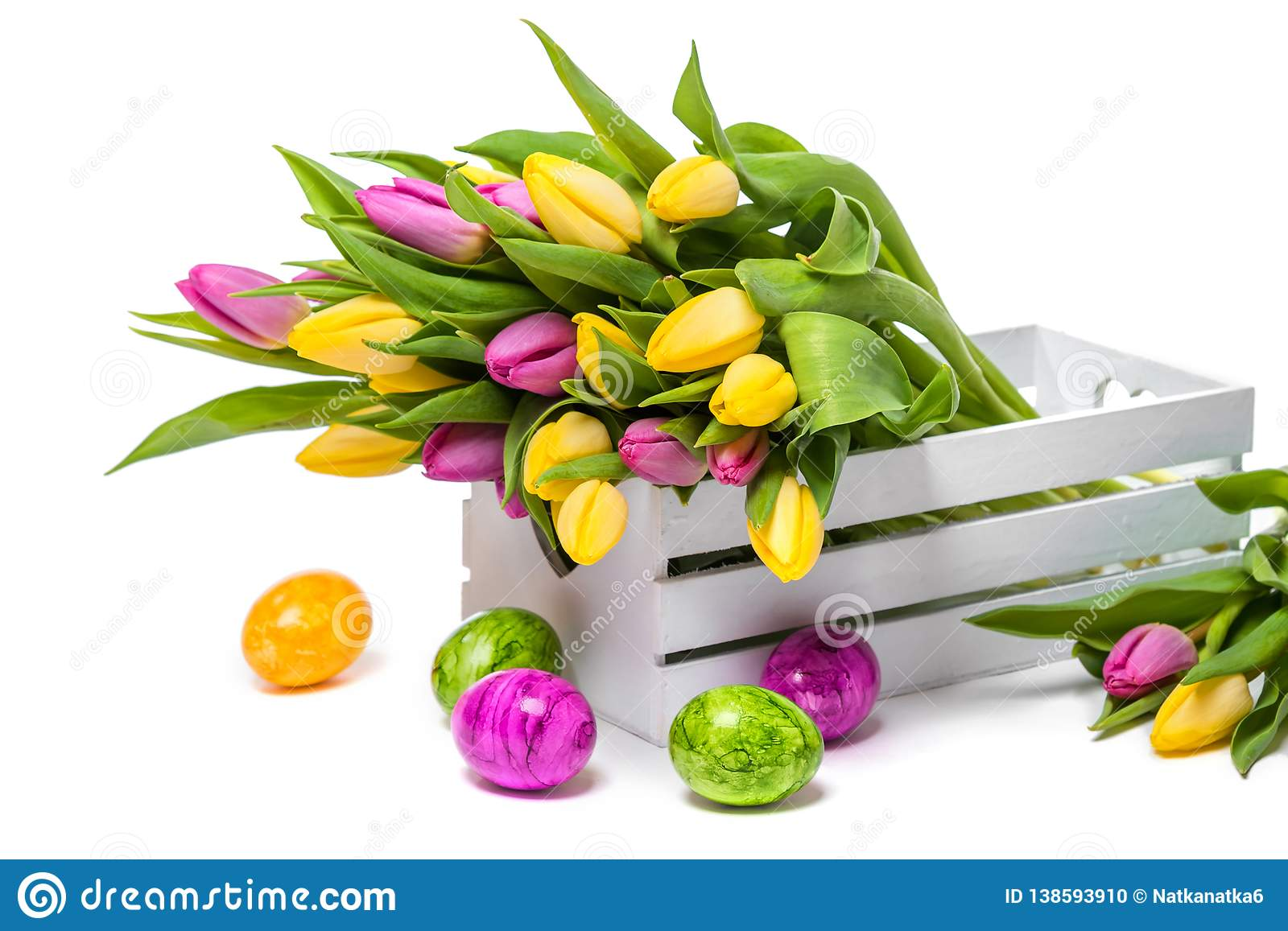 Easter eggs and a bunch of colorful tulips in a white wooden box on a white background