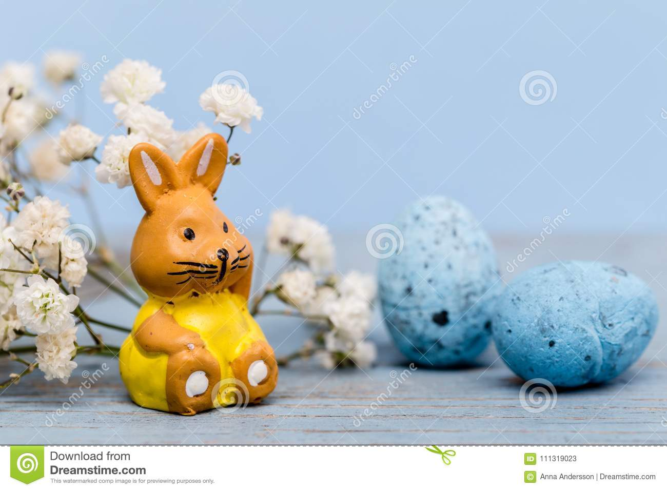 Easter background with eggs and a easter bunny and white flowers on blue paper