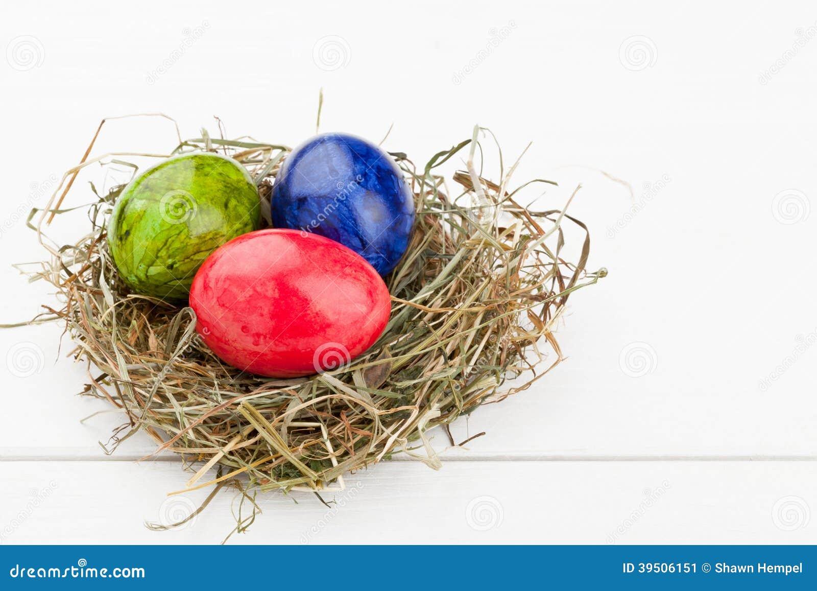 Easter eggs in hay nest on white wood