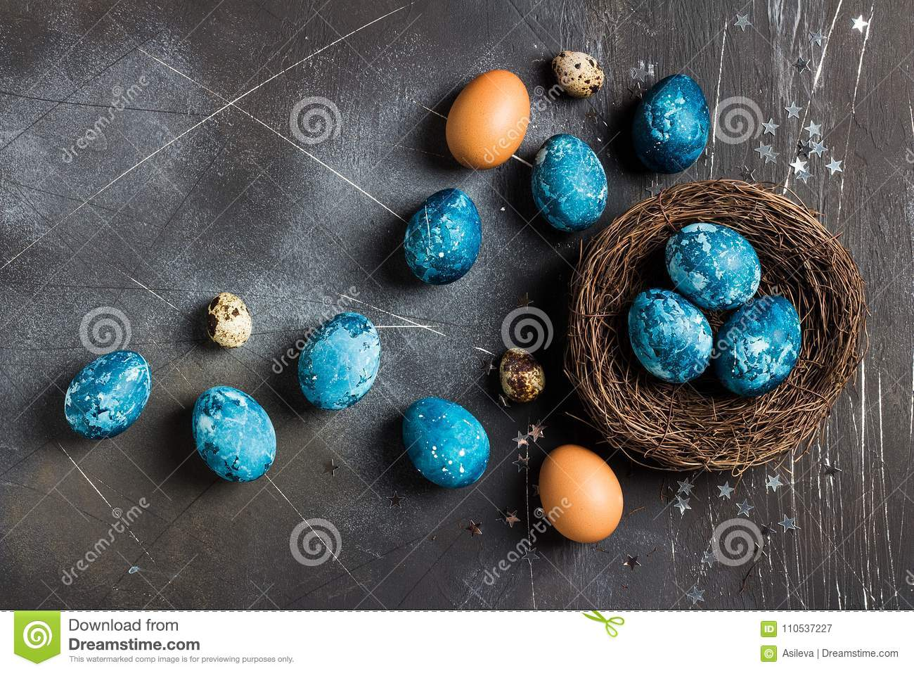 Easter eggs in nest painted by hand in blue color on dark background