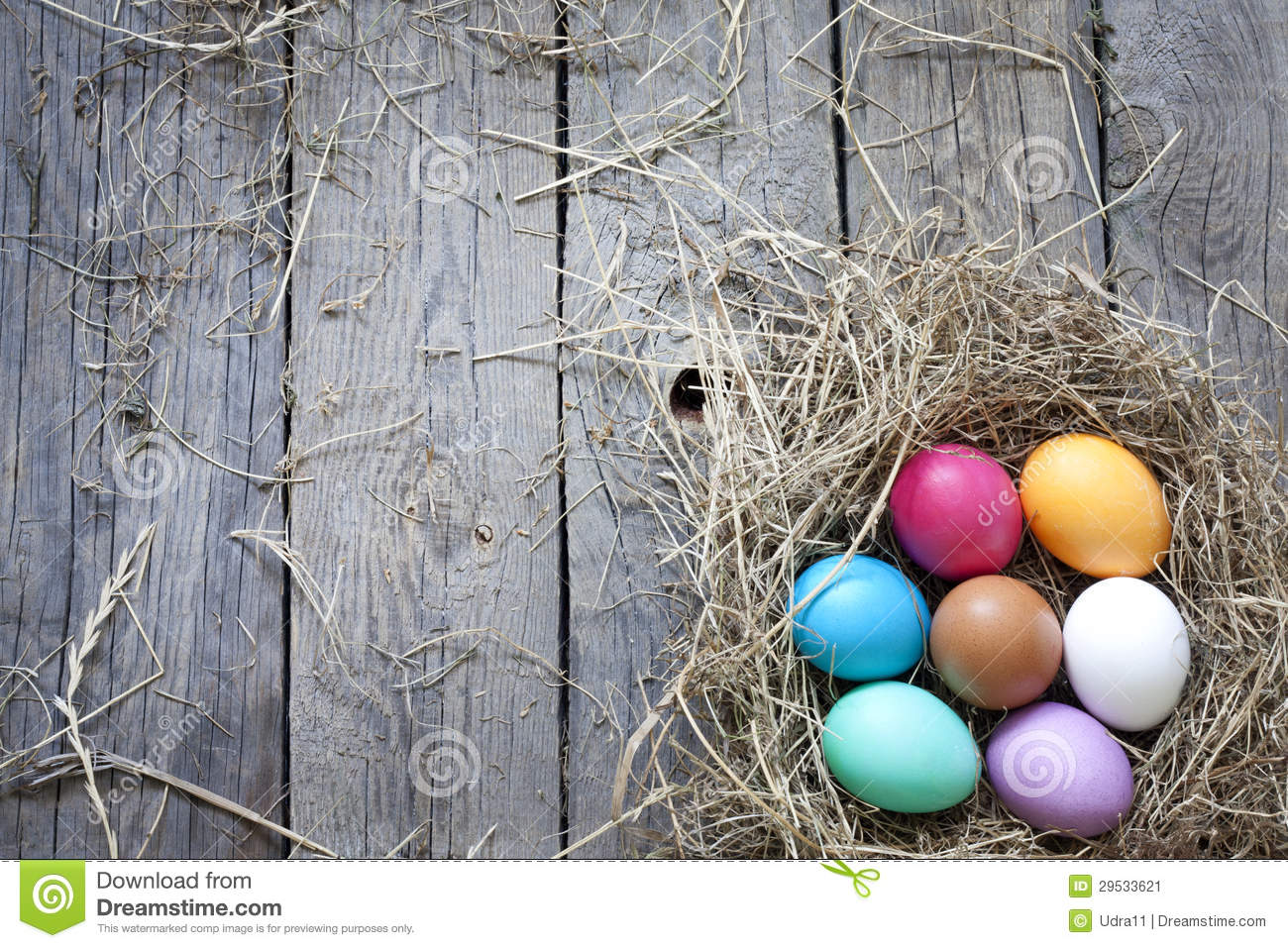 Easter eggs in nest on vintage wooden boards