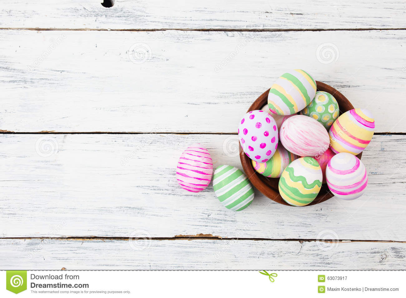Easter eggs painted in pastel colors on white wood