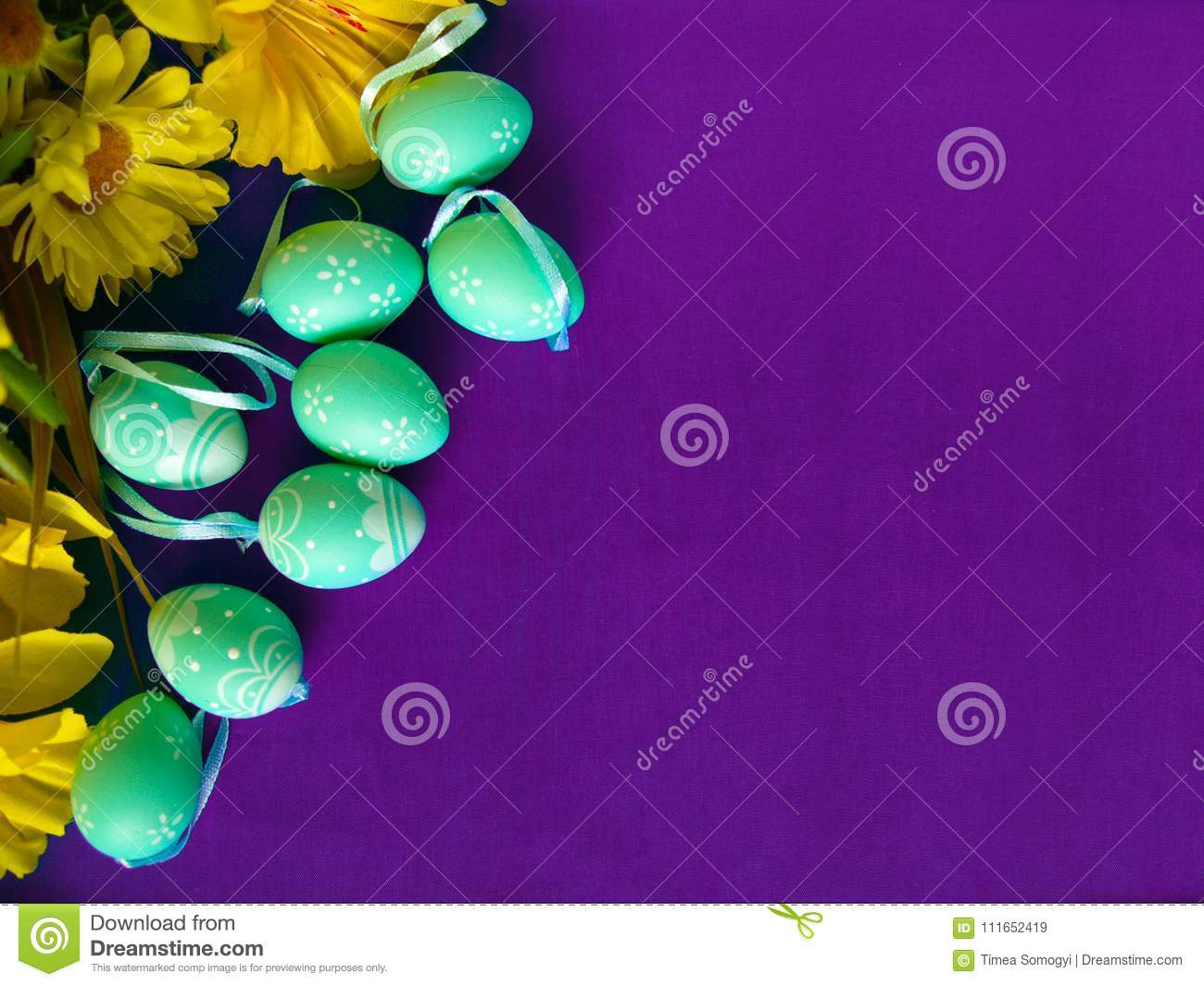Easter eggs on purple silk, with yellow flowers.