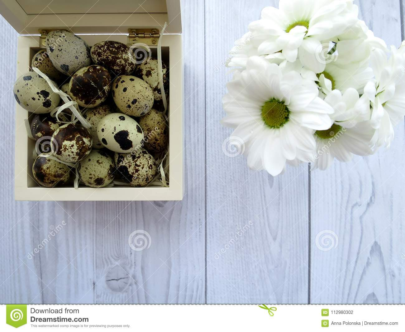 Easter eggs and white flowers on a white wooden table