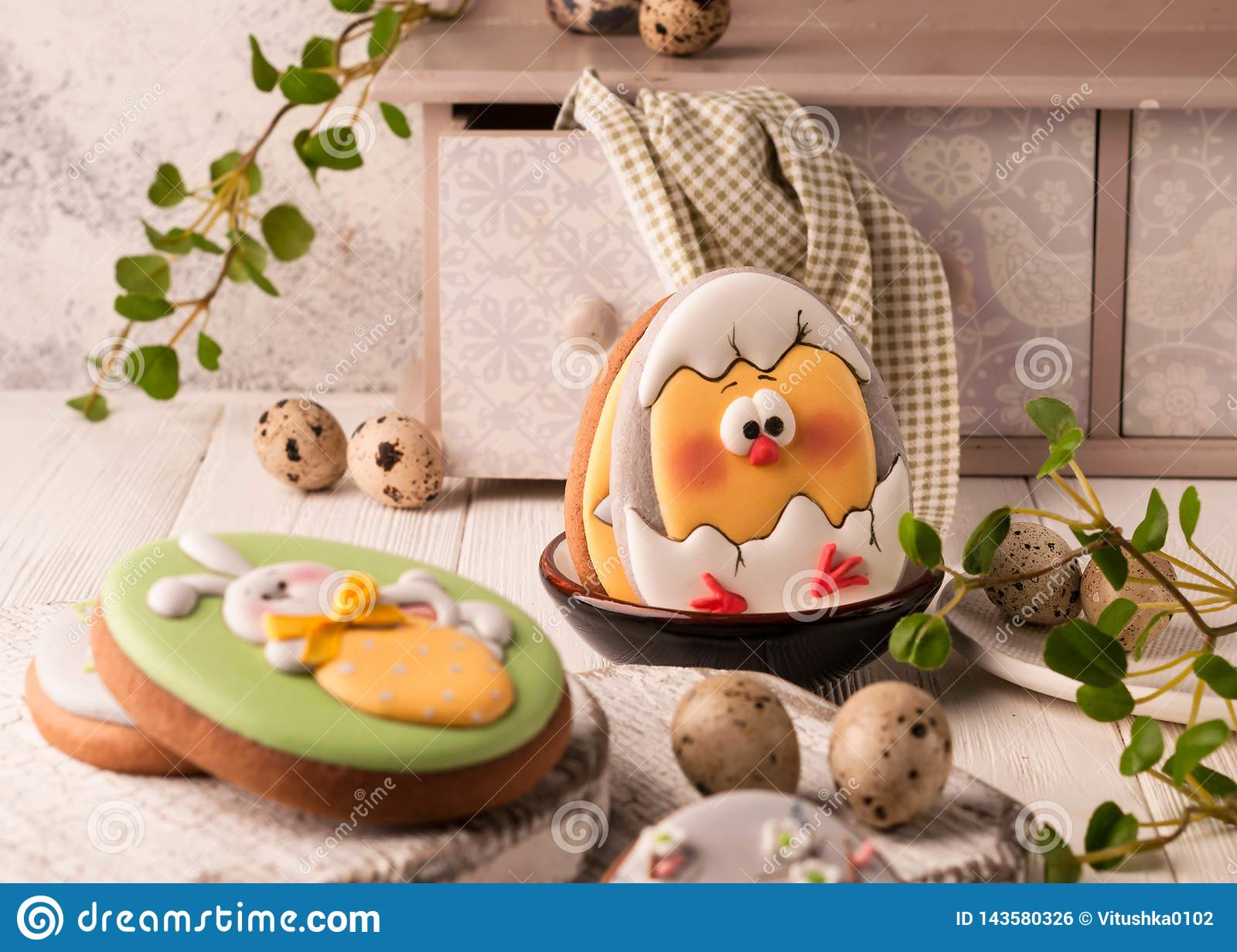 easter green cookies with painted easter bunny and hatched chicken in bowl near quail eggs, decorative sideboard and napkin