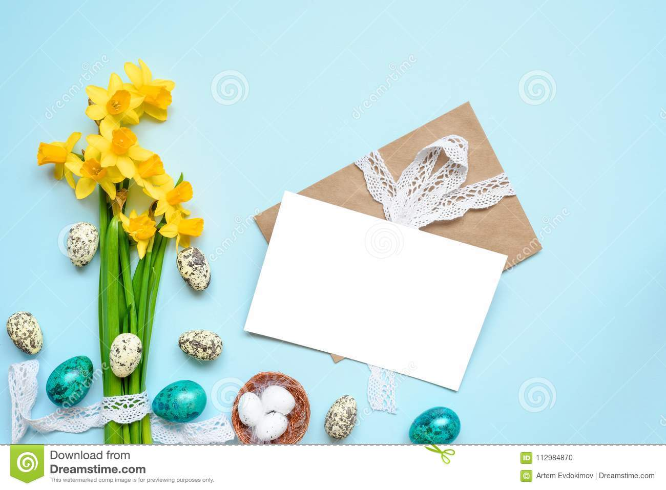 Easter greeting card with easter eggs and spring flowers mock up over blue background. mock up