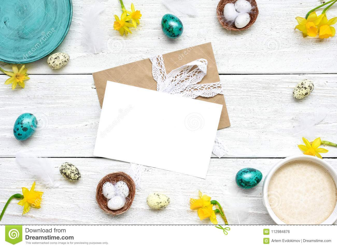 Easter greeting card in frame made of quail eggs, cup of cappuccino and spring flowers on white wooden background