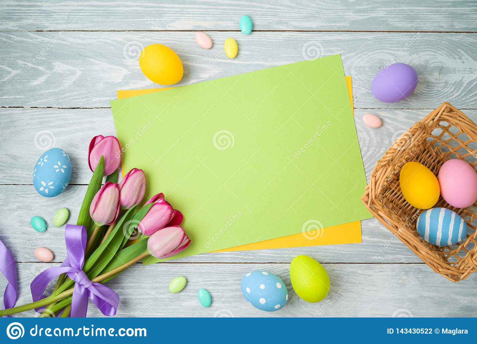 Easter holiday background with paper note, easter eggs in basket and tulip flowers on wooden table