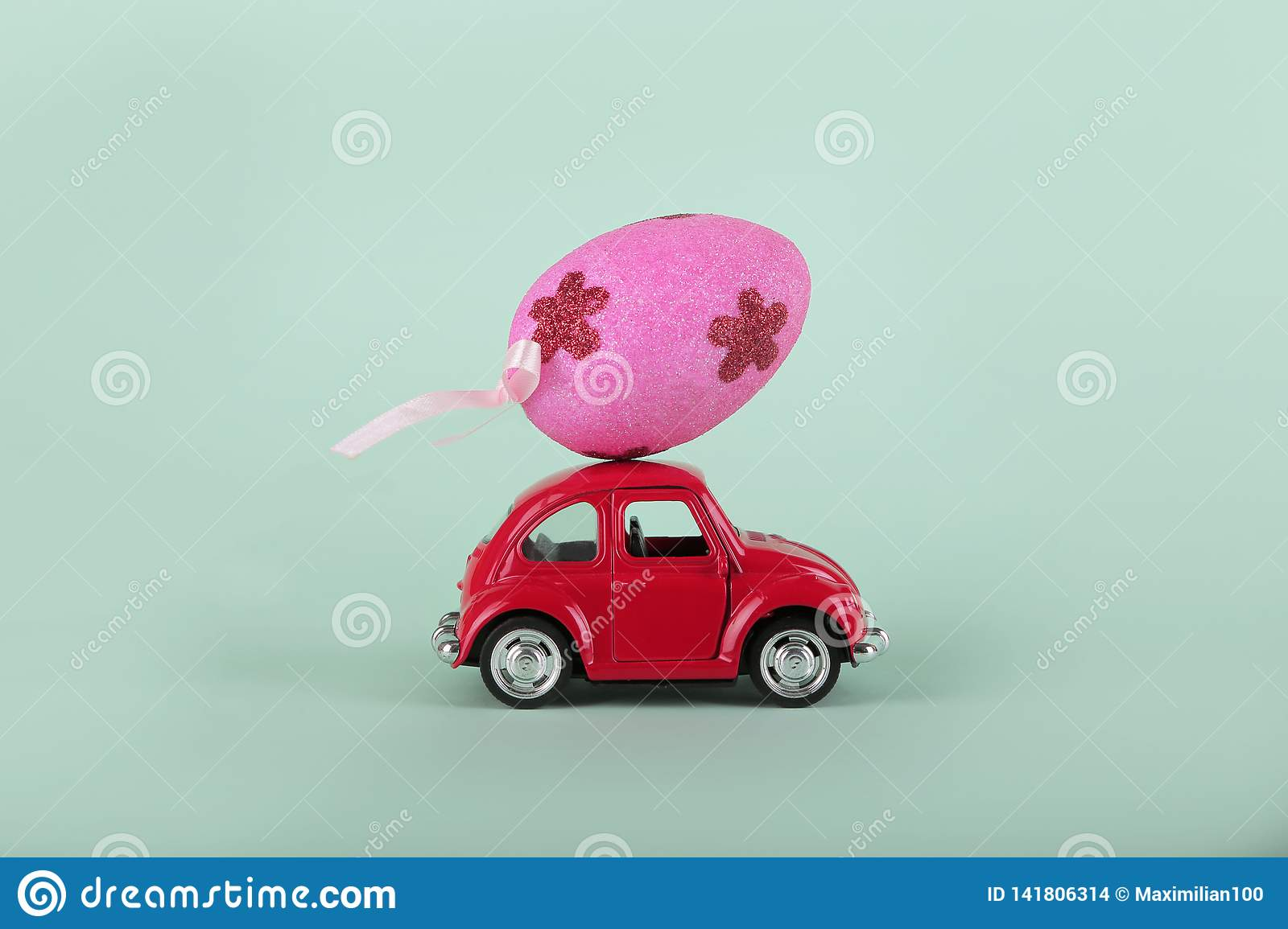 Easter holiday concept with egg on toy red car on turquoise background.
