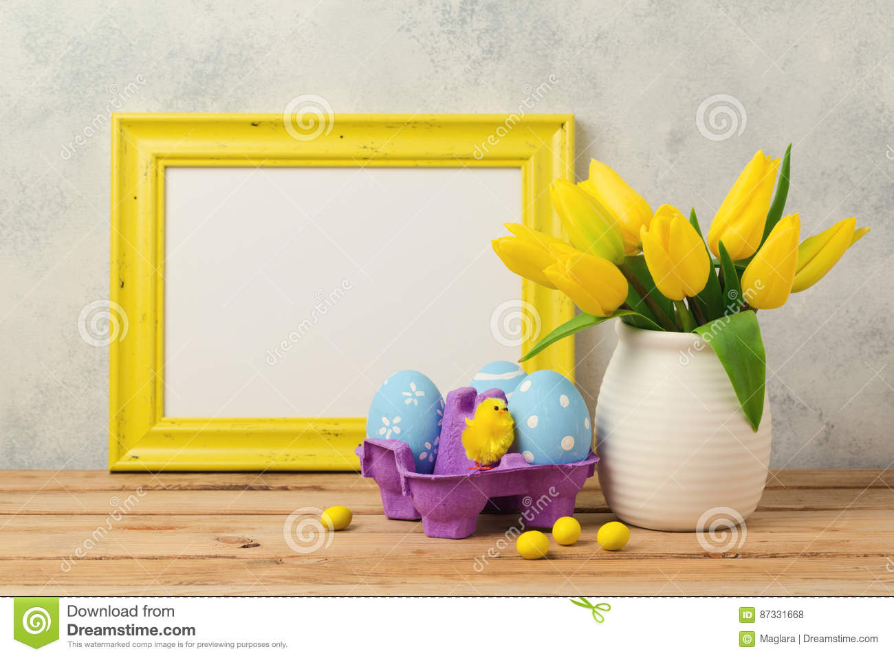 Easter holiday concept with tulip flowers, eggs decorations and blank photo frame