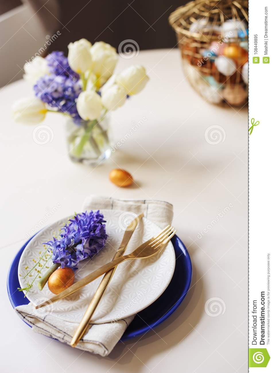 Easter holiday festive dining table with plate, golden cutlery, painted eggs and hyacinth flower on white background