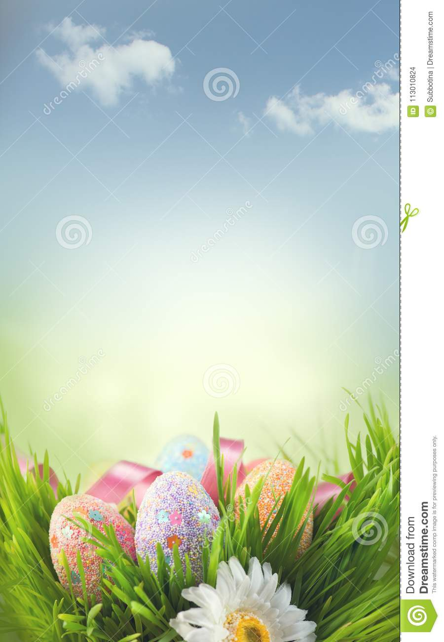 Easter holiday scene background. Traditional painted colorful eggs in spring grass over blue sky