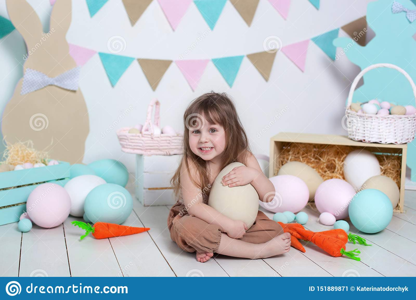 Easter! Little girl in overalls sits with a large Easter egg. Easter location, decorations. Family holidays, traditions. Colorful