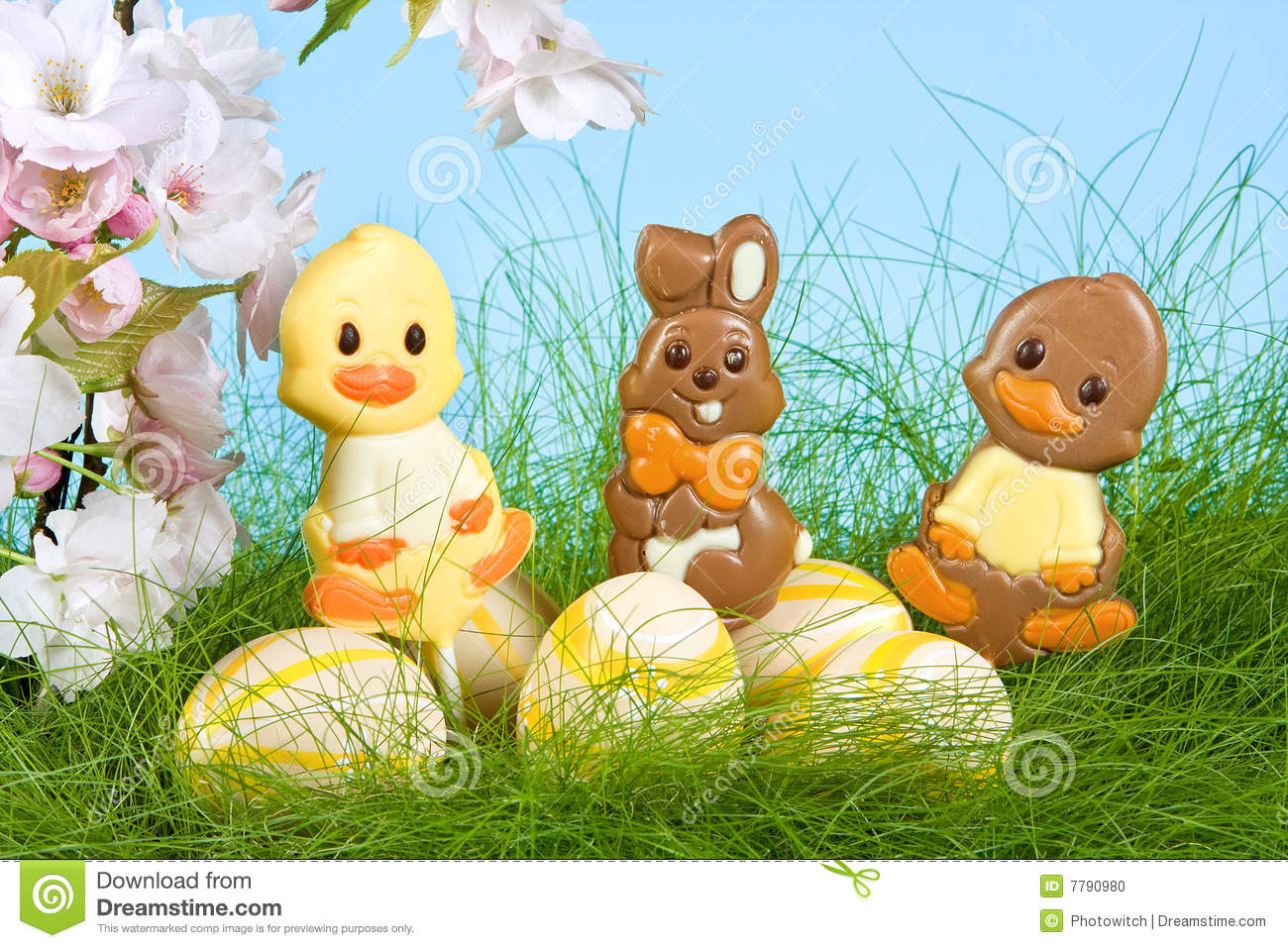 Three chocolate easter lollies under spring blossoms.