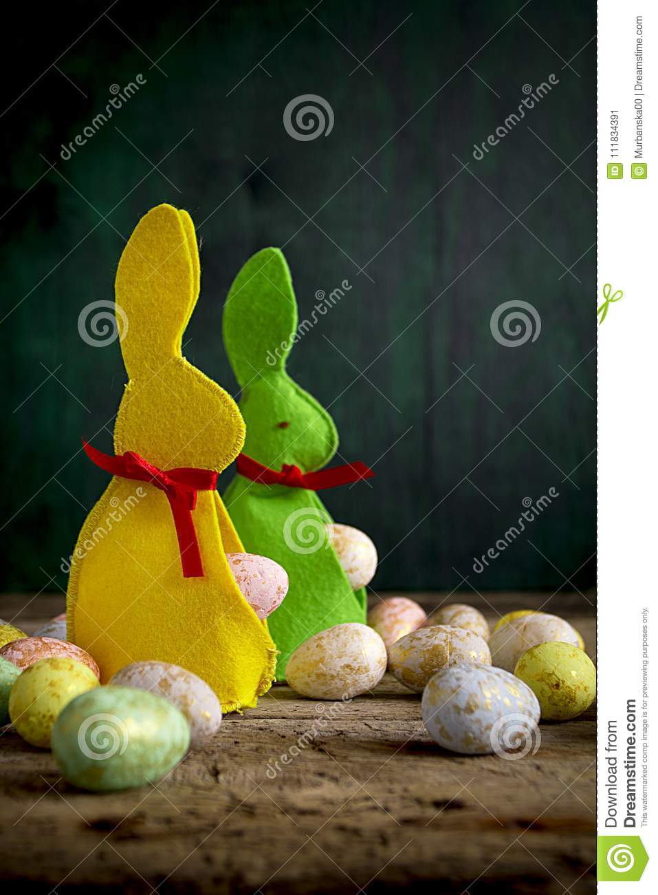 Easter rabbits with eggs on wooden table.