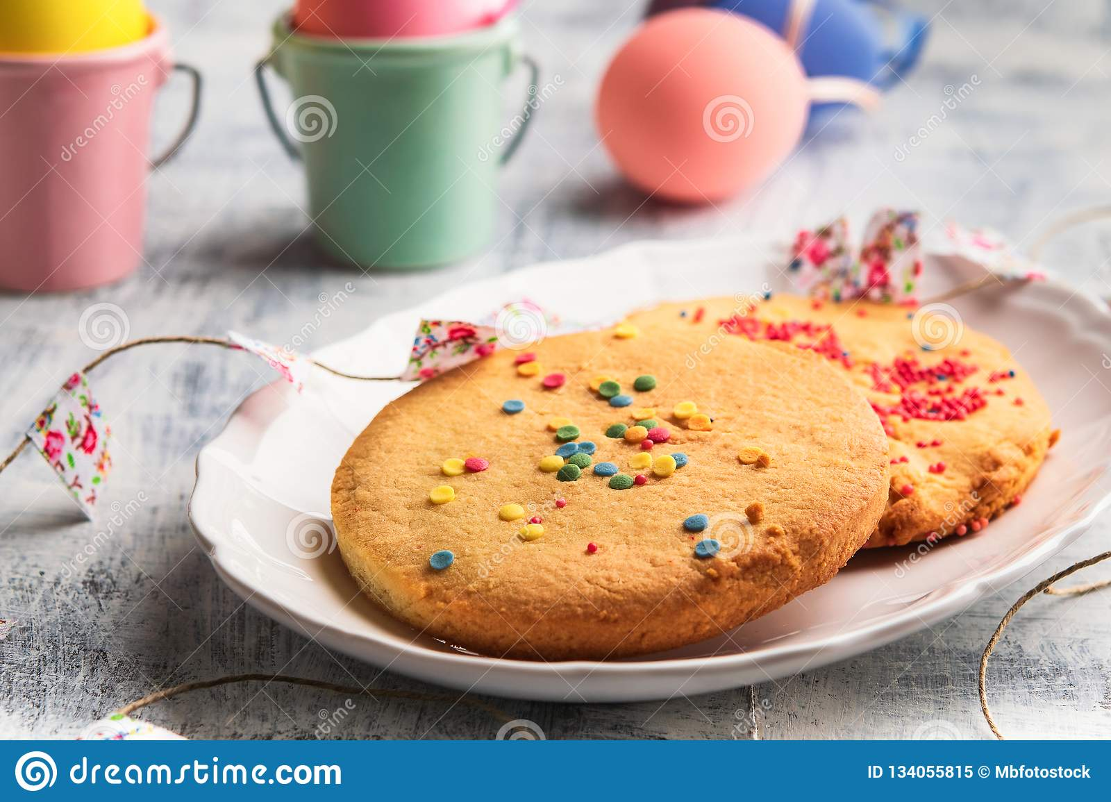 Easter Spring Cookies with colorful sprinkles on a white plate. Easter happy concept