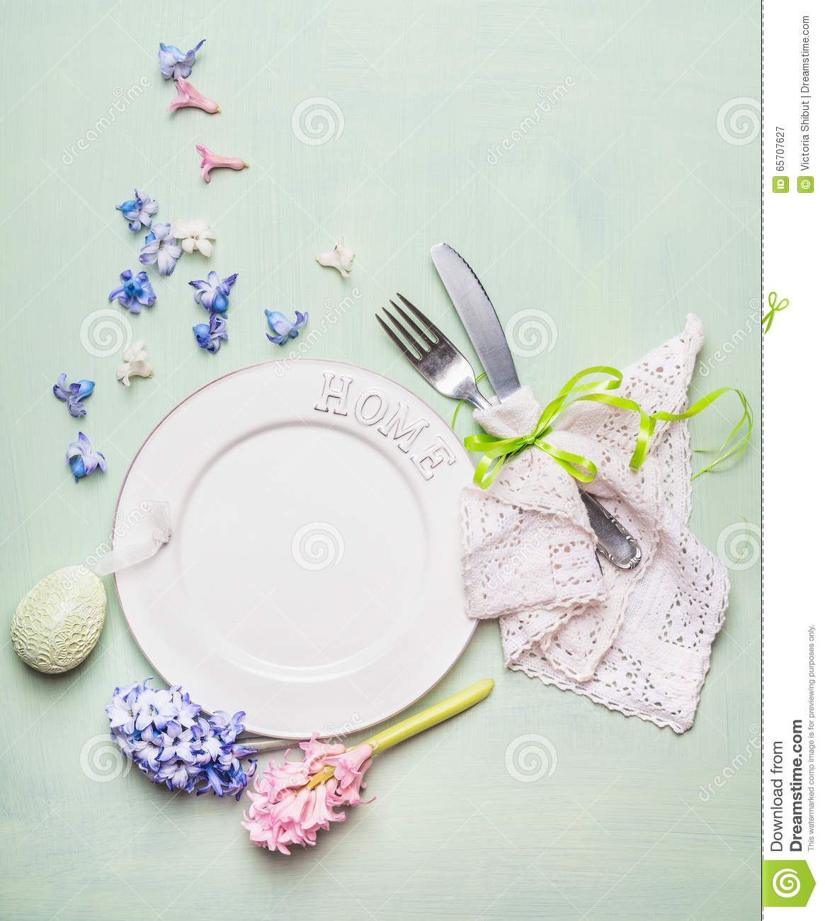 Easter table place setting with blank plate, hyacinths flowers decoration, cutlery and decor egg on light green background, top v
