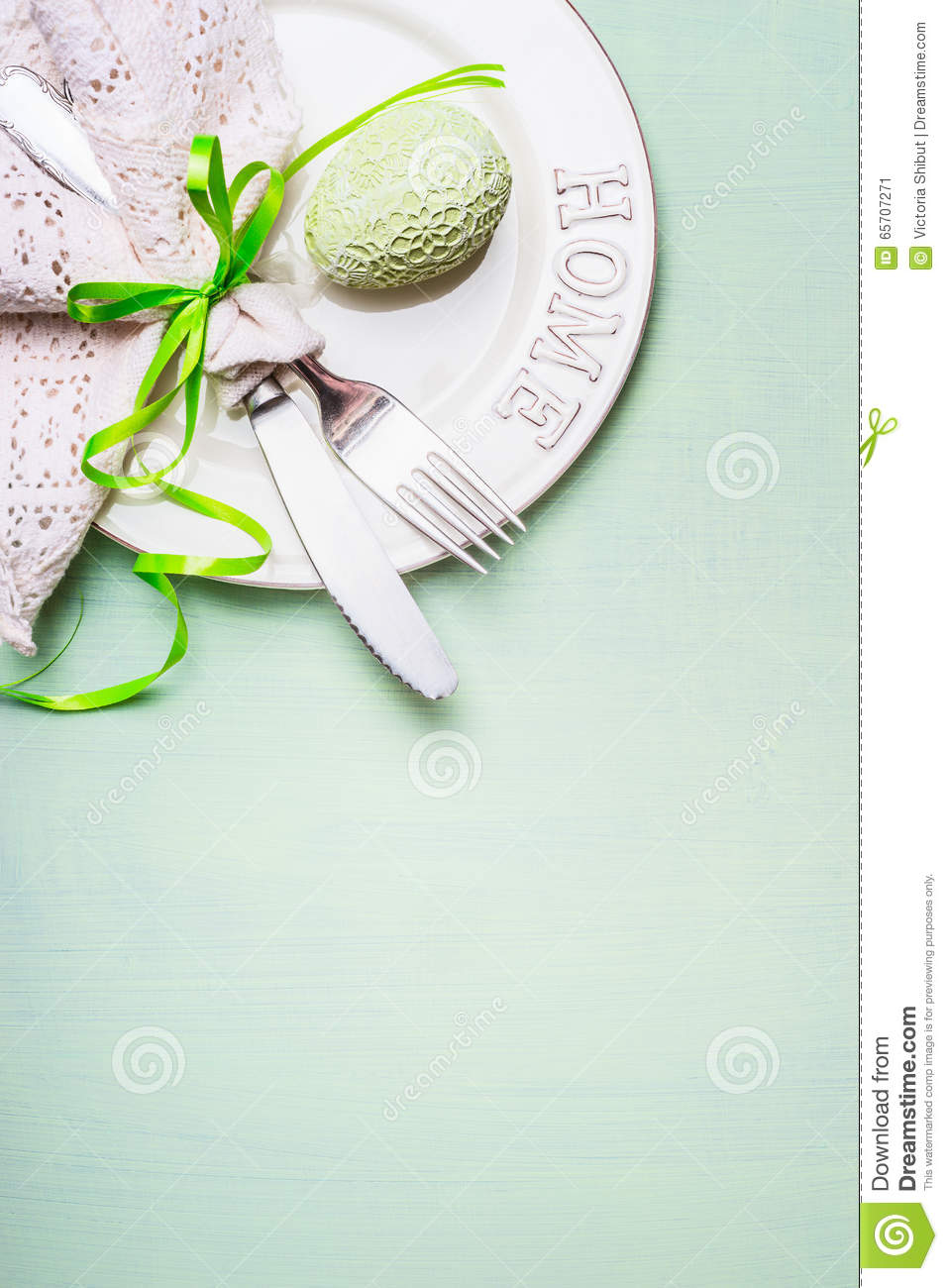 Easter table place setting with plate, cutlery decorated with lacy napkin and egg on light green background, top view.